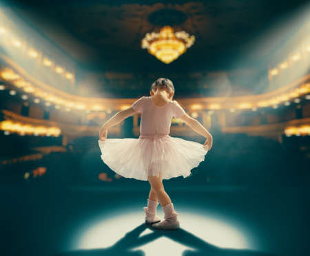 Photo pour Cute little girl dreaming of becoming a ballerina. Child girl in a pink tutu dancing on the stage. Baby girl is studying ballet. - image libre de droit