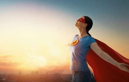 Foto de Joyful beautiful young woman in superhero costume posing on sunset background. - Imagen libre de derechos