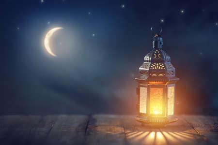 Foto de Ornamental Arabic lantern with burning candle glowing at night. Festive greeting card, invitation for Muslim holy month Ramadan Kareem. - Imagen libre de derechos