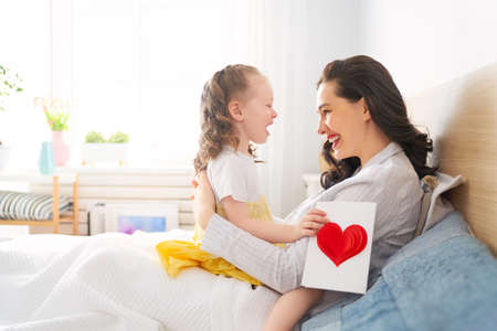 Photo for Happy mother's day! Child daughter is congratulating mom and giving her postcard and gift. Mum and girl smiling and hugging. Family holiday and togetherness. - Royalty Free Image