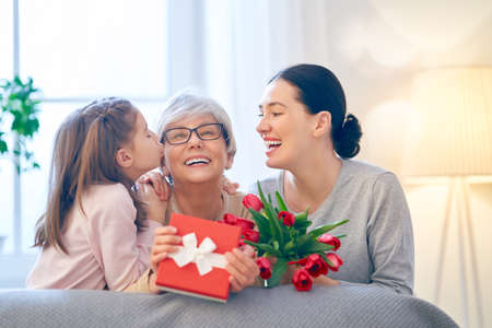 Photo for Happy mother's day! Child and mom congratulating  granny giving her flowers tulips ang gift box. Grandma, mum and girl smiling and hugging. Family holiday and togetherness. - Royalty Free Image