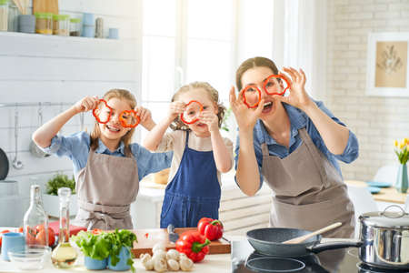 Foto de Healthy food at home. Happy family in the kitchen. Mother and children daughters are preparing vegetables. - Imagen libre de derechos