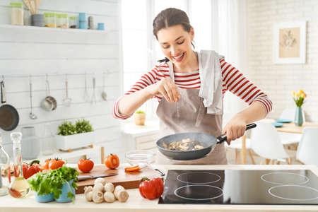 Foto de Healthy food at home. Happy woman is preparing the proper meal in the kitchen. - Imagen libre de derechos