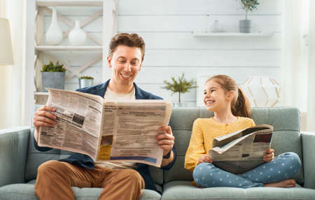 Photo pour Happy loving family. Daddy and his daughter child girl are reading newspapers together. Father's day concept. - image libre de droit