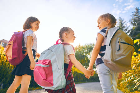 Photo pour Pupils of primary school. Girls with backpacks outdoors. Beginning of lessons. First day of fall. - image libre de droit
