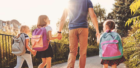 Photo for Parent and pupils of primary school are going hand in hand. Man and girls with backpacks behind backs. Beginning of lessons. First day of fall. - Royalty Free Image