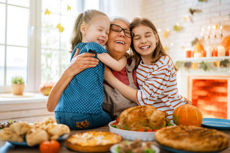 Photo pour Happy Thanksgiving Day! Autumn feast. Family sitting at the table and celebrating holiday. Traditional dinner. Grandmother and granddaughters. - image libre de droit