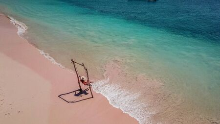 Foto de A girl swinging on the beach swing on Pink Beach, Lombok, Indonesia. Captured from above with a drone. The water changes colors from turquoise to navy blue. beach has a nice coral color. - Imagen libre de derechos