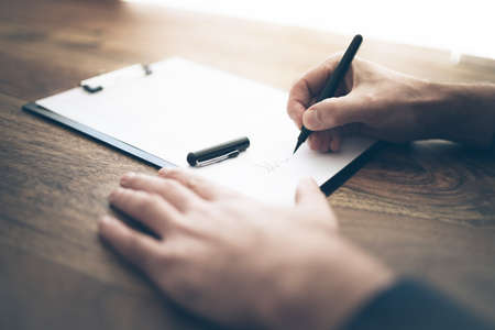 Photo for close-up shot of businessman signing contract or document on wooden desk - Royalty Free Image