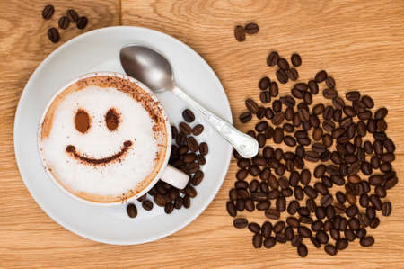 Cappuccino coffee with smiley face on wooden table, overhead view