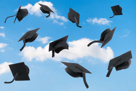 Graduation mortar boards thrown into a blue sky