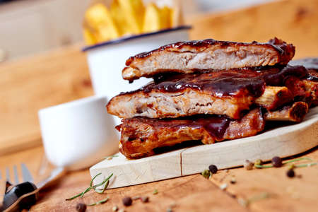 Photo for Barbecue ribs with fries on wooden table - Royalty Free Image