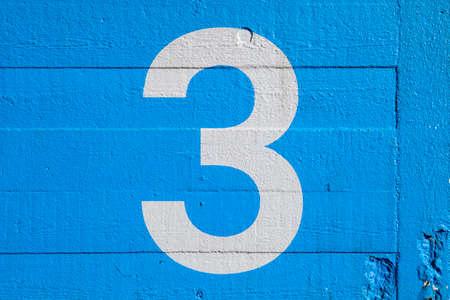 Foto de The Number 3 painted on a blue wall. - Imagen libre de derechos