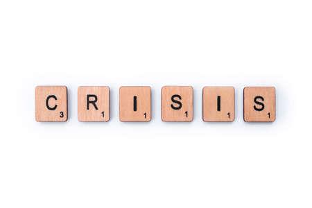 Foto de London, UK - February 6th 2019: The word CRISIS, spelt out with wooden letter Scrabble tiles. - Imagen libre de derechos
