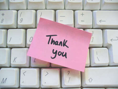 thank you message post-it note on a computer keyboard