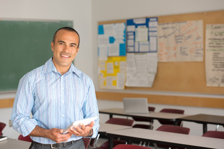 Foto de This image shows a Hispanic Male Teacher in his classroom - Imagen libre de derechos