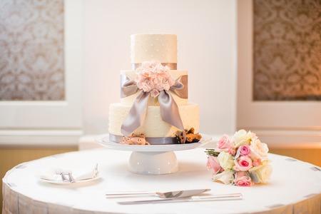 Photo pour White wedding cake and bouquet with Roses, Dusty Miller, Ranunculus - image libre de droit
