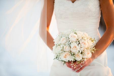 Foto de Bride holding wedding bouquet with Roses and Baby?s breath flowers - Imagen libre de derechos