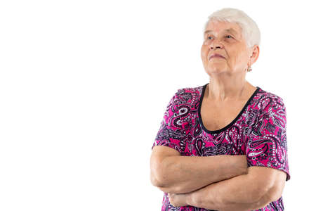 Elderly lady with arms crossed looking up on white background