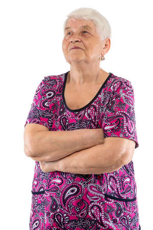 Elderly woman with arms crossed looking up on white background
