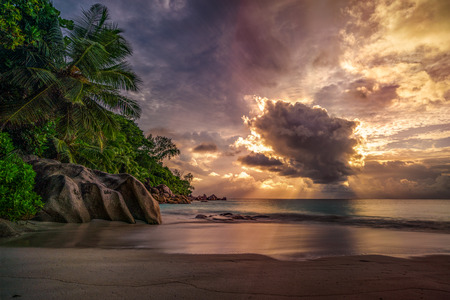 Foto de Sunbeams during sunset behind a big cloud at anse georgette on praslin on the seychelles - Imagen libre de derechos