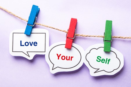 Photo pour Love your self paper bubbles with clip hanging on the line against purple background. - image libre de droit