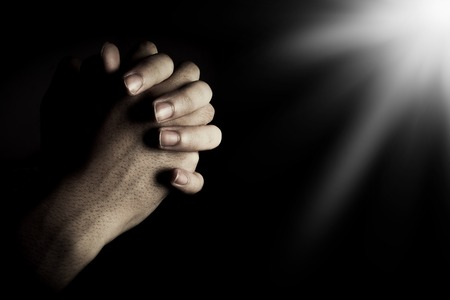 Photo pour Praying hands is in the dark with light on the hands. - image libre de droit