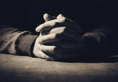 Photo pour Praying hands of young man on a wooden desk background. - image libre de droit