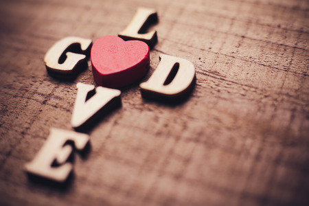Foto de God is love concept text lying on the rustic wooden background. - Imagen libre de derechos
