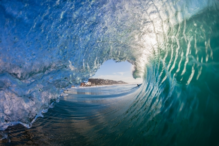 Photo pour Inside hollow crashing morning waves with water detail from surfing or swimmers view - image libre de droit