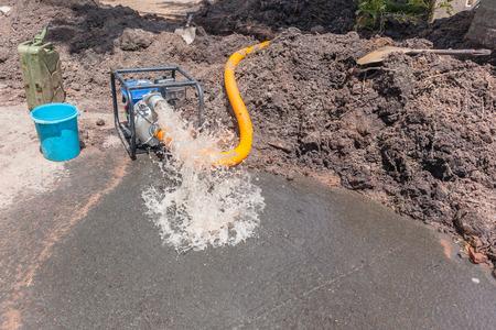 Foto de Plumbing pumping water from earthwork trench digging repairs of broken main  pipe in residential road area with mobile portable motor pump draining damage. - Imagen libre de derechos