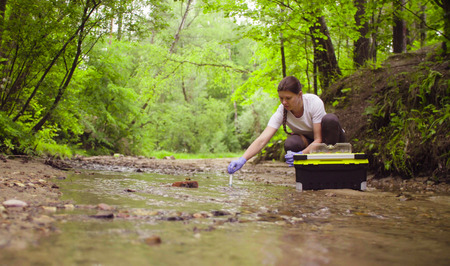 Photo pour Woman ecologist taking samples of water from the creek - image libre de droit
