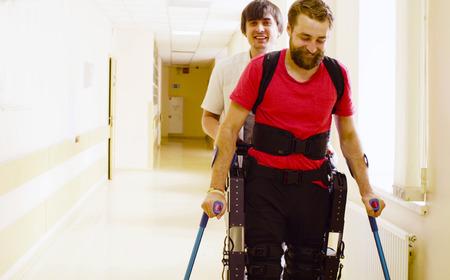Foto de Young disable man in the robotic exoskeleton - Imagen libre de derechos