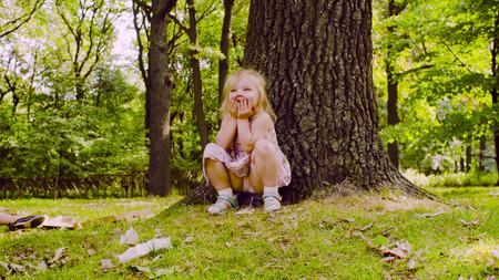 Photo pour A girl sitting in the park on the grass - image libre de droit