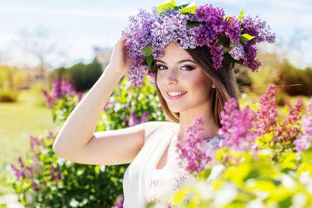 Beautiful smiling girl is wearing beautiful wreath of lilac flowers