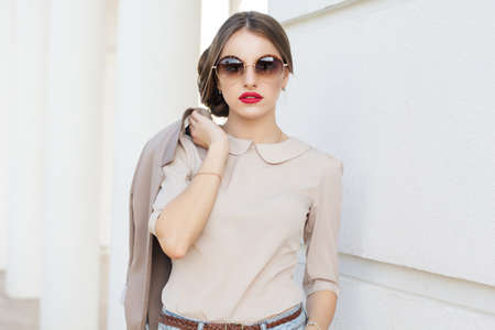 Photo for Beautiful lady is wearing sunglasses and holding jacket , business style - Royalty Free Image