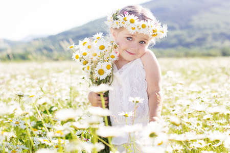 Cute little smiling girl in the chamomile field in spring