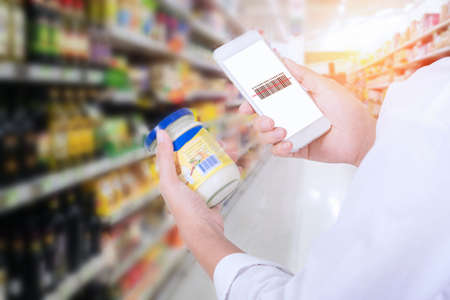 Photo pour Woman scanning barcode from a label in a supermarket with mobile phone - image libre de droit