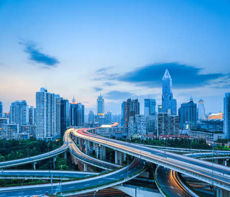 Photo pour complicated highway intersection with modern city skyline at dusk in shanghai , road transportation infrastructure.  - image libre de droit