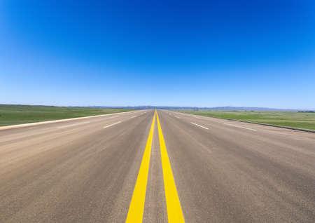 Photo pour wide road in prairie against a blue sky - image libre de droit
