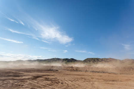 Foto per the dust was blowing in busy construction site against a blue sky - Immagine Royalty Free