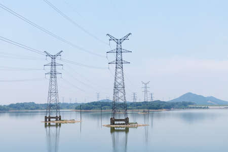 Foto de power transmission tower closeup on the lake - Imagen libre de derechos
