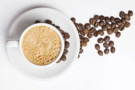 Foto de Delicious breakfast cup of coffee top view with foam and roasted bean decoration. - Imagen libre de derechos