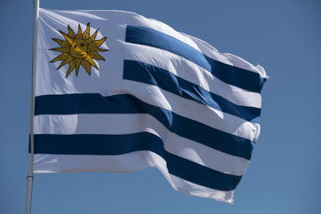 Foto de Uruguay country flag waving in the wind on blue sky background. National south american uruguayan emblem. - Imagen libre de derechos