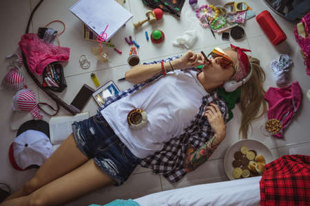 Photo pour after studying blonde student, lying on the floor in headphones and sunglasses, listening to music and smoking a cigarette. The image of a modern student, education, Accessories of a modern young girl - image libre de droit
