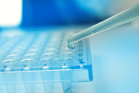 Foto de Pipette dropping stem cell research fluid on pcr plate. Medical Dropper - Imagen libre de derechos