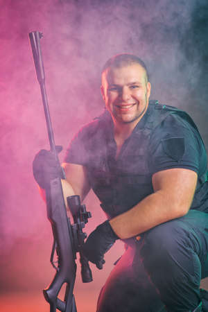 Foto de Soldier comes out of the smoke on the battlefield. The concept of military special operations. Kneeling and smiling - Imagen libre de derechos