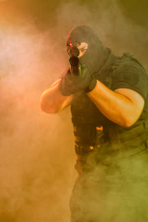 Foto de Soldier comes out of the smoke on the battlefield. The concept of military special operations. Aim at the target - Imagen libre de derechos