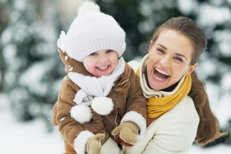 Foto de Portrait of happy mother and baby in winter park - Imagen libre de derechos