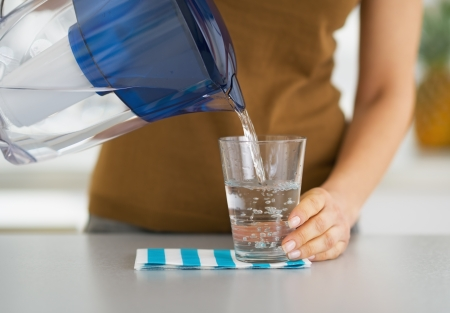 Photo for Closeup on housewife pouring water into glass from water filter pitcher - Royalty Free Image